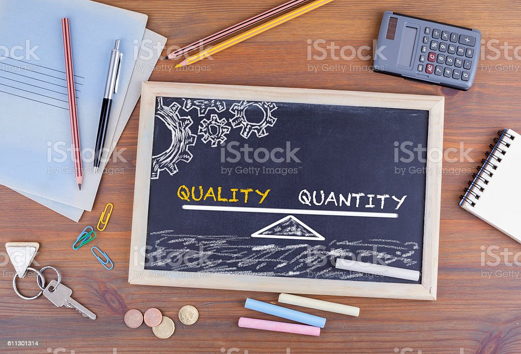 Quality Quantity Balance. Chalkboard on wooden office desk stock photo