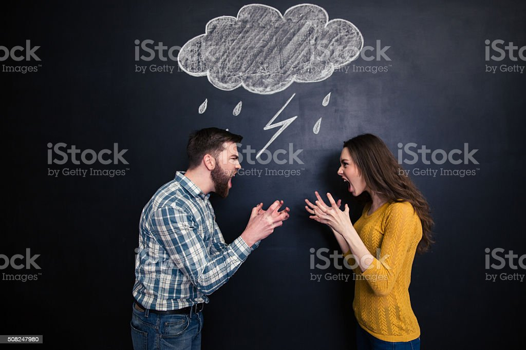 Quarrelling couple standing against background of chalkboard and screaming stock photo