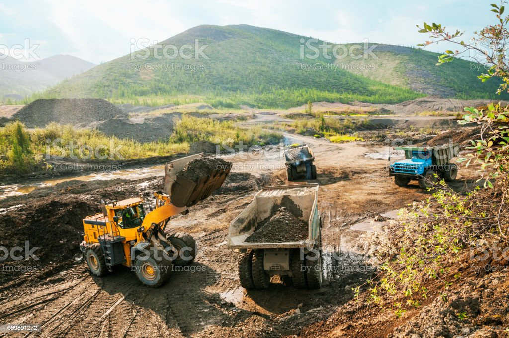 Quarry dumpers in operation, loading of soil by means of excavator - loader stock photo
