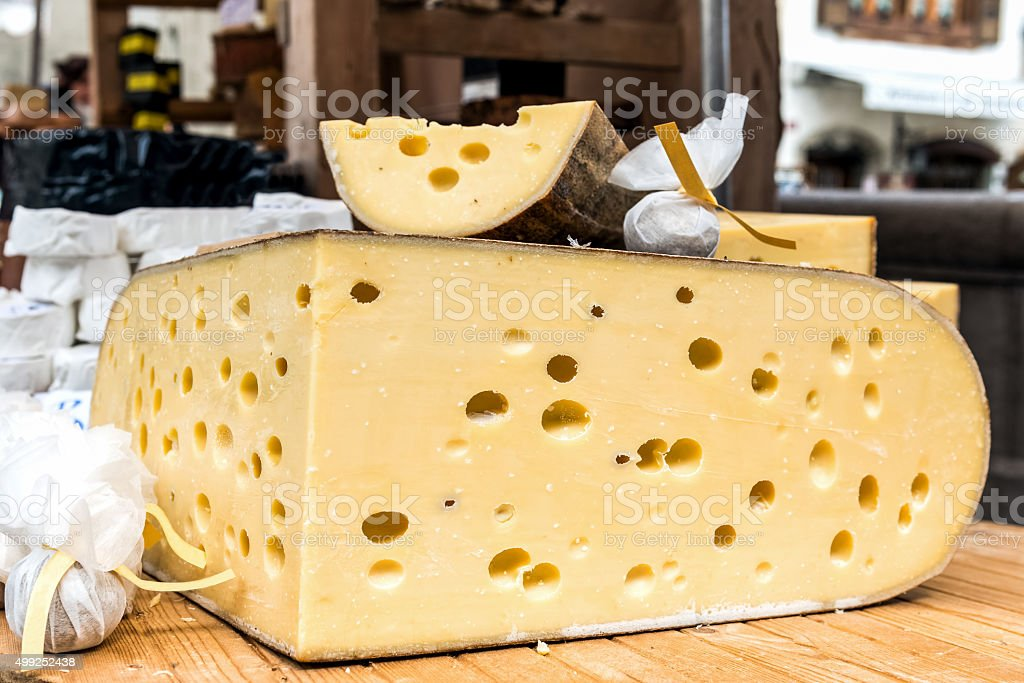 Quarter of Emmental cheese head on the market place. stock photo