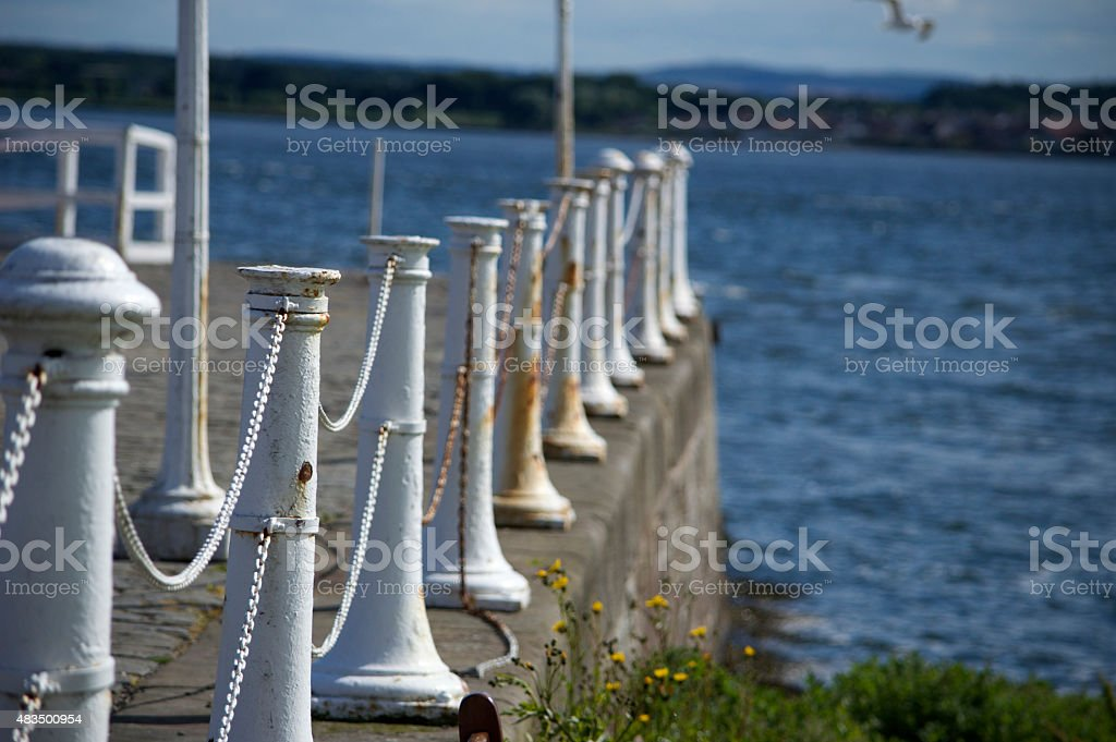 Quayside lined with white bollards and chains stock photo