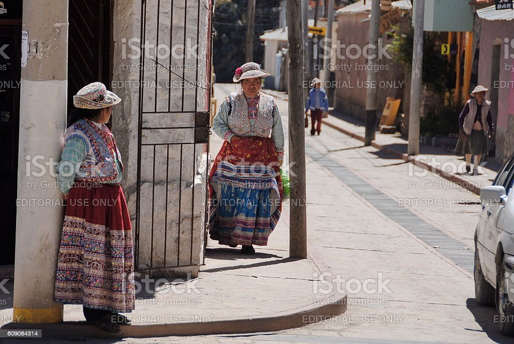 Quechua women dressed in traditional skirts on street, Yankey, Peru. stock photo