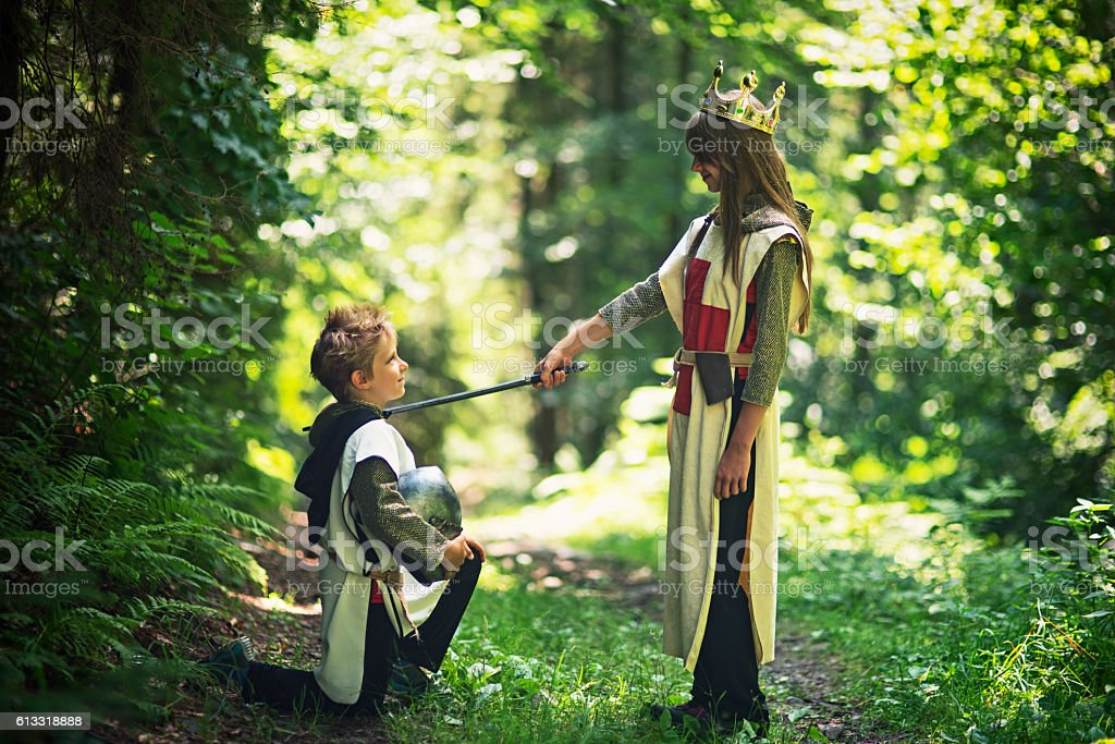 Queen knighting her loyal knight in forest stock photo