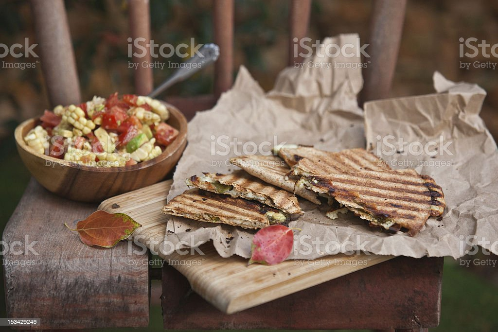 Quesadilla wedges on cutting board with bowl of corn salsa royalty-free stock photo