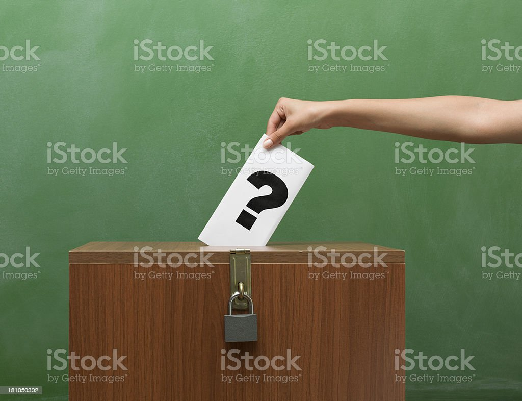 Question Mark Ballot Being Used to Vote, Against Blackboard royalty-free stock photo
