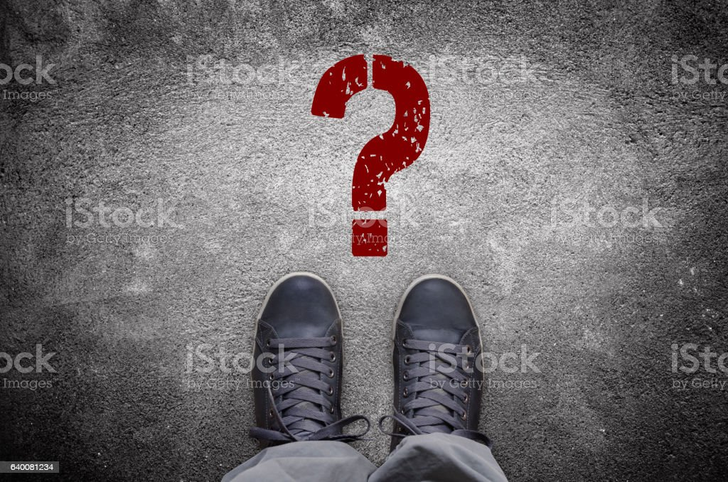 Question mark stencil print on asphalt road with sneakers stock photo