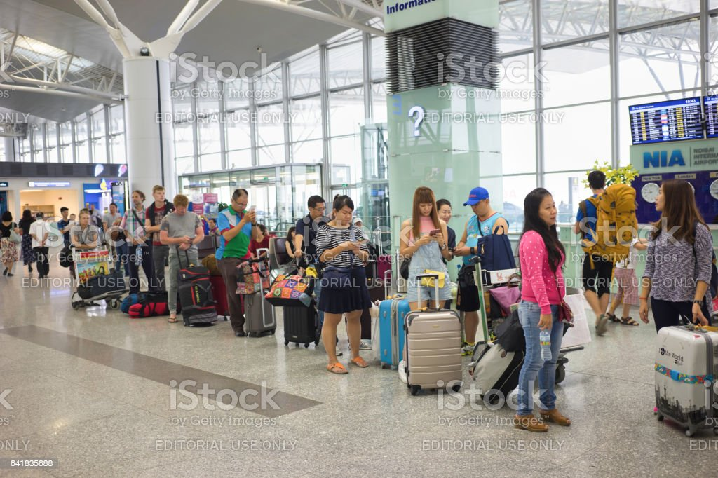 Hanoi, Vietnam - Apr 29, 2016: Queue of Asian people in line waiting at boarding gate in Noi Bai airport stock photo