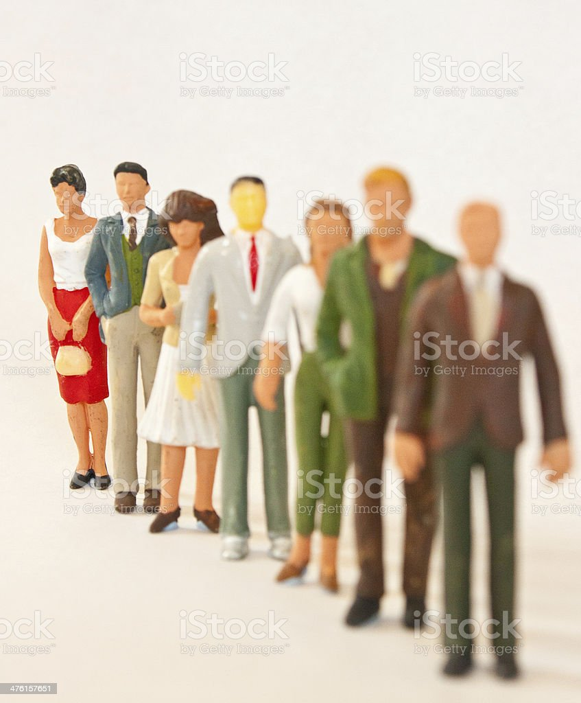 Queue of figures with focus on the last figure stock photo