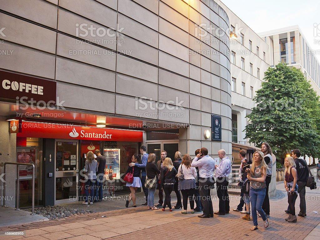 Queue of people waiting at a Santander ATM; central Edinburgh stock photo