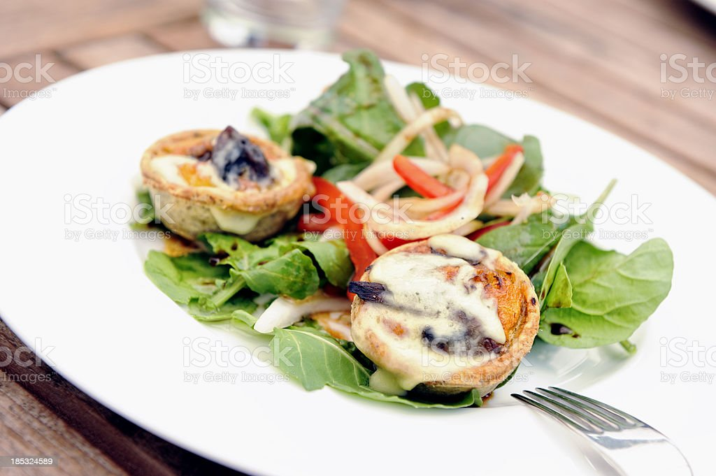 Quiche on fresh summer salad stock photo