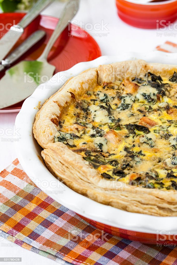 quiche with salmon and wild herbs stock photo