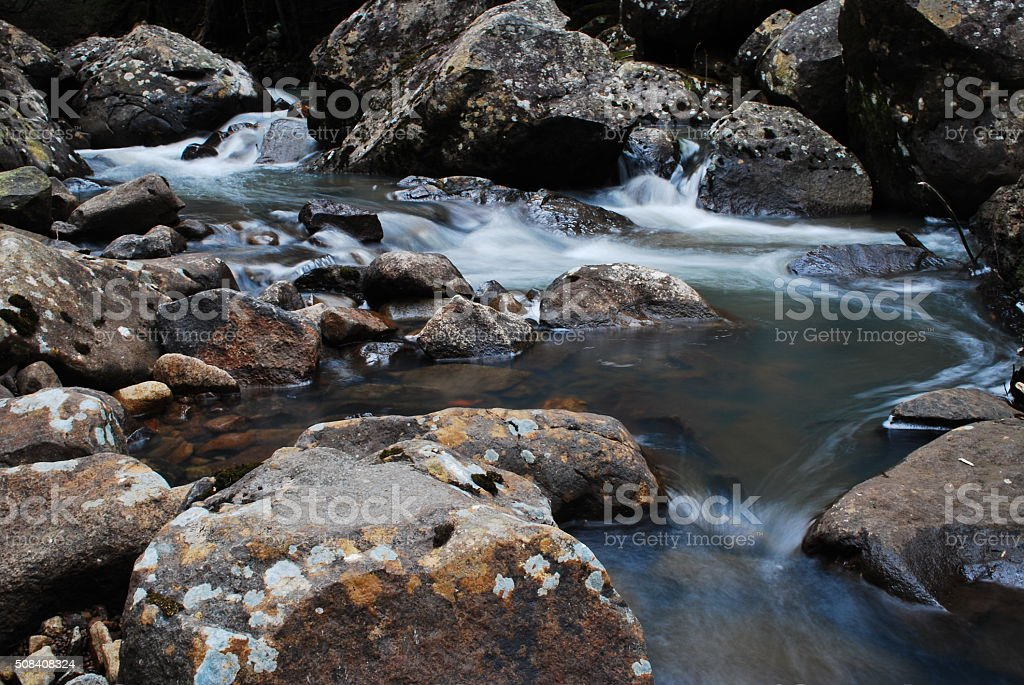 Quick flowing stream amongst Lichen coloured rocks stock photo