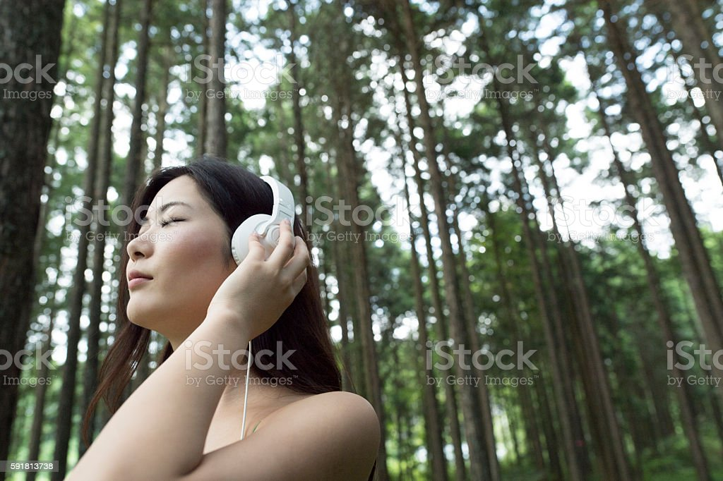 Quiet girl listening to music in the forest. stock photo
