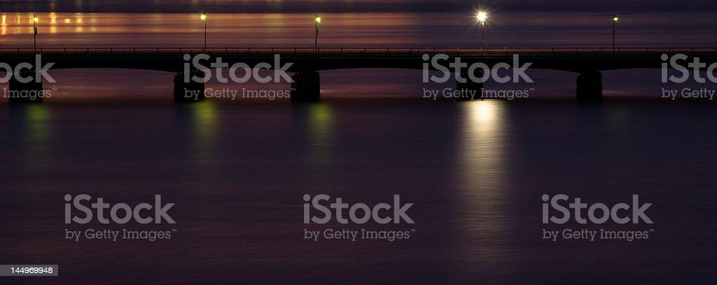 Quiet, Lonely Bridge Illuminated on River at Twilight royalty-free stock photo