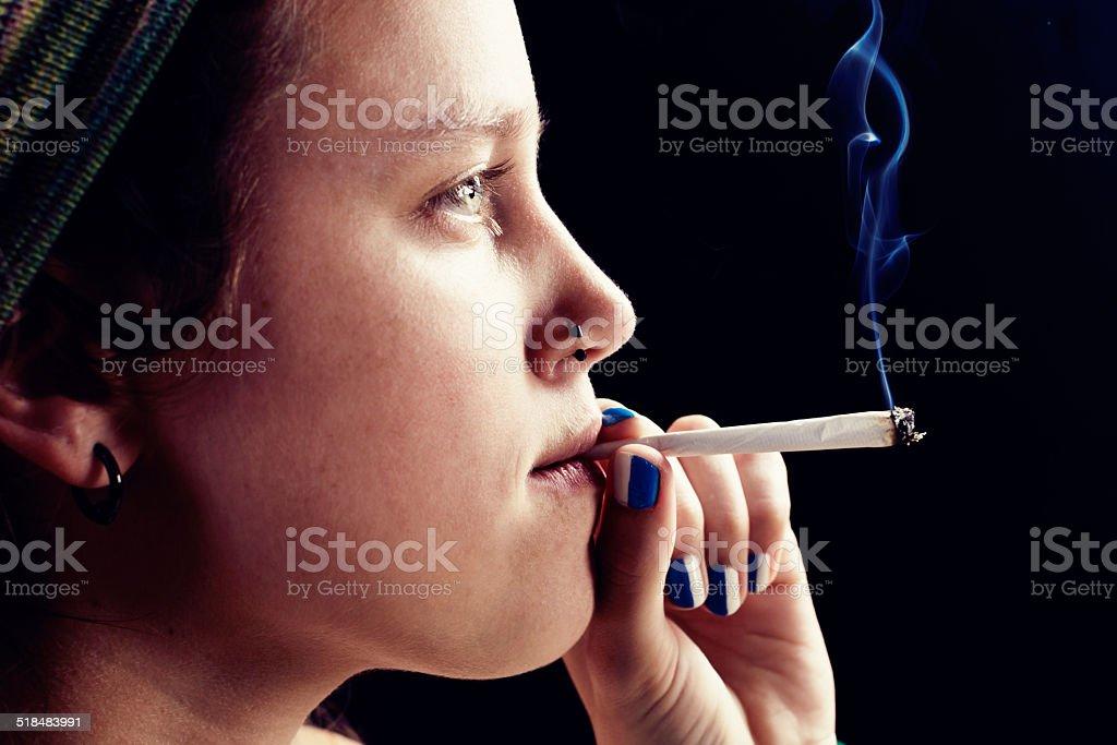 Quiet rebel thoughtfullly smoking marjuana cigarette stock photo