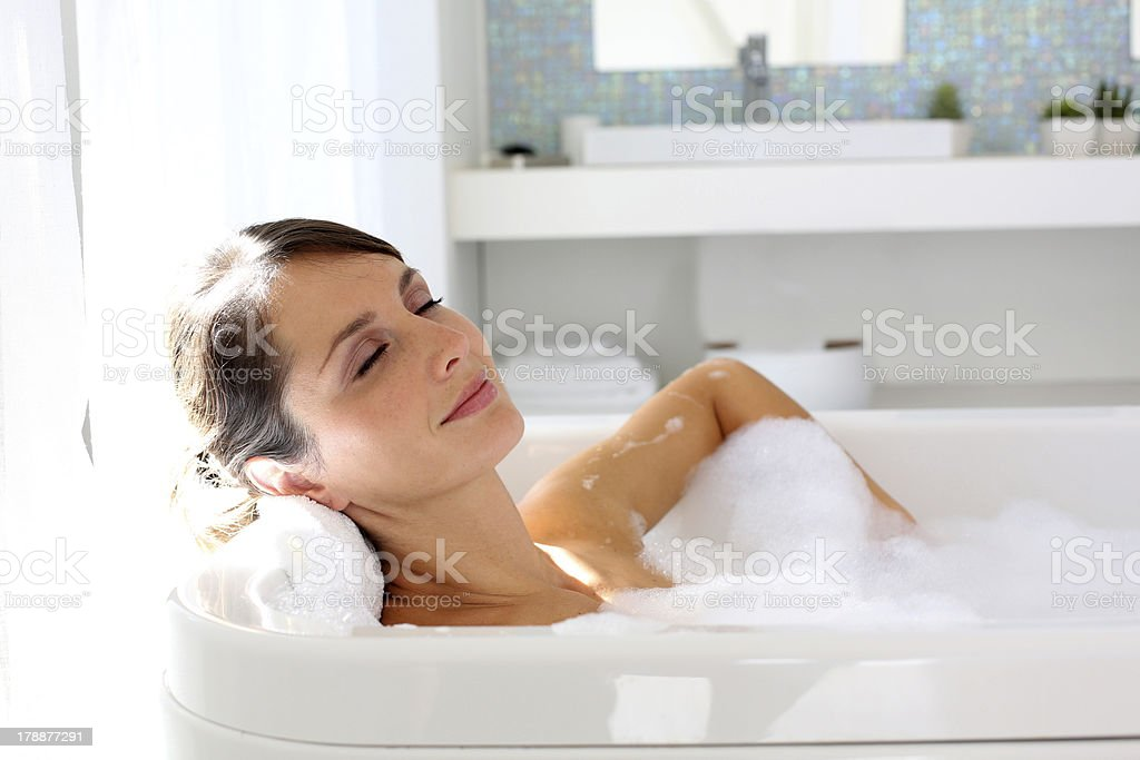 Quiet woman resting in a big bathtub stock photo
