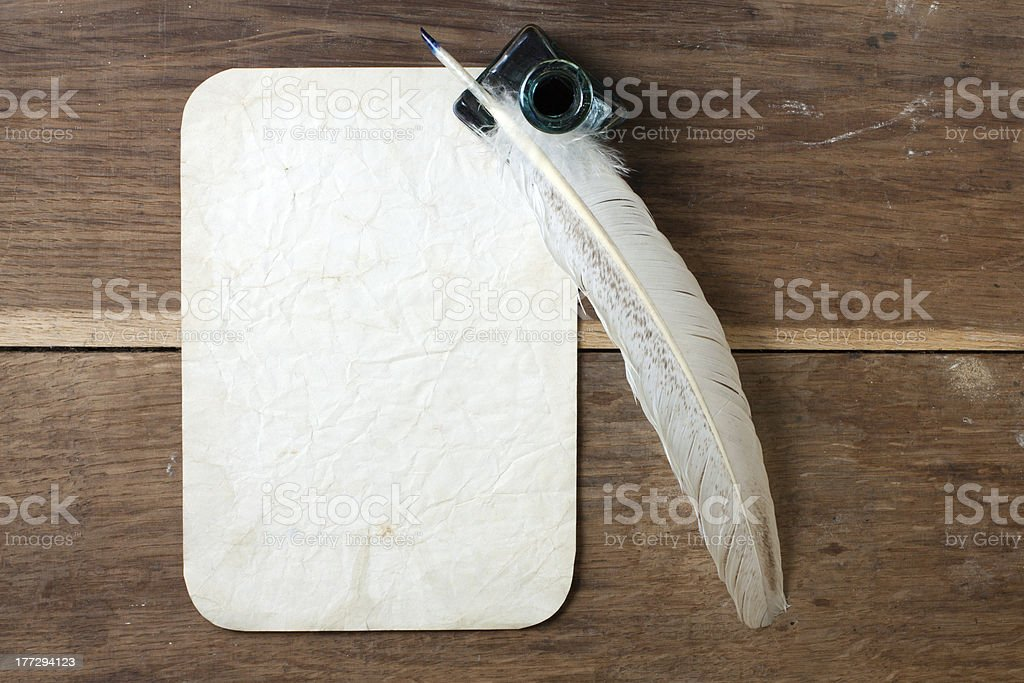 Quill and inkwell, old grunge paper on wood background royalty-free stock photo