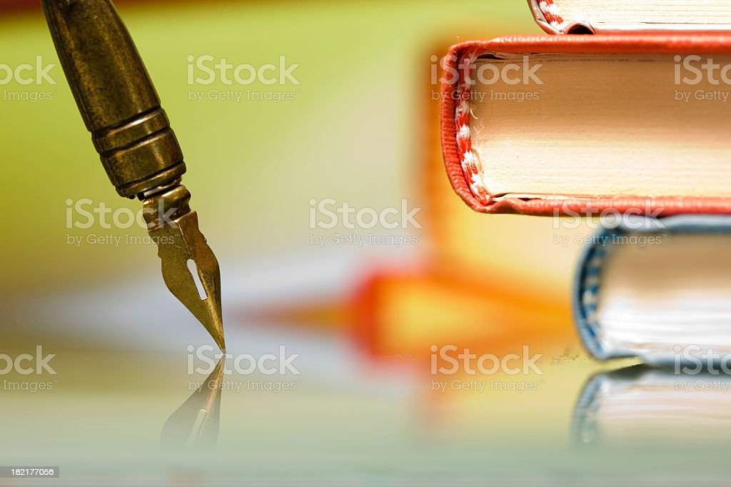 A quill pen and two books in a pile royalty-free stock photo