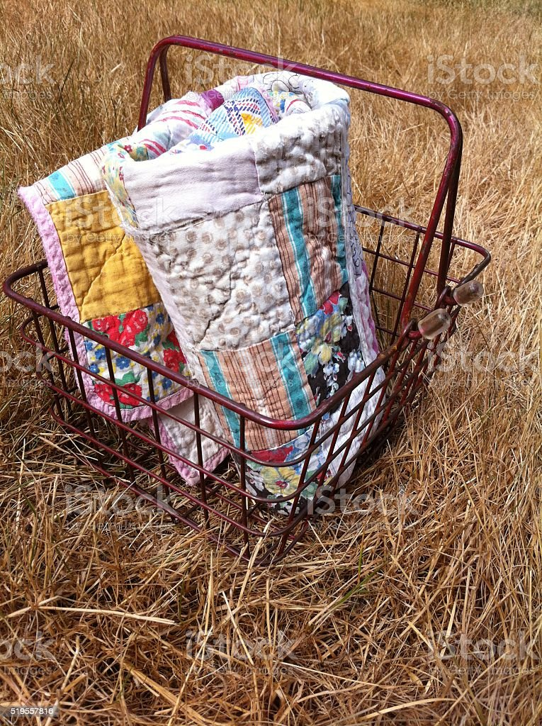 Quilt folded into a basket on grass stock photo
