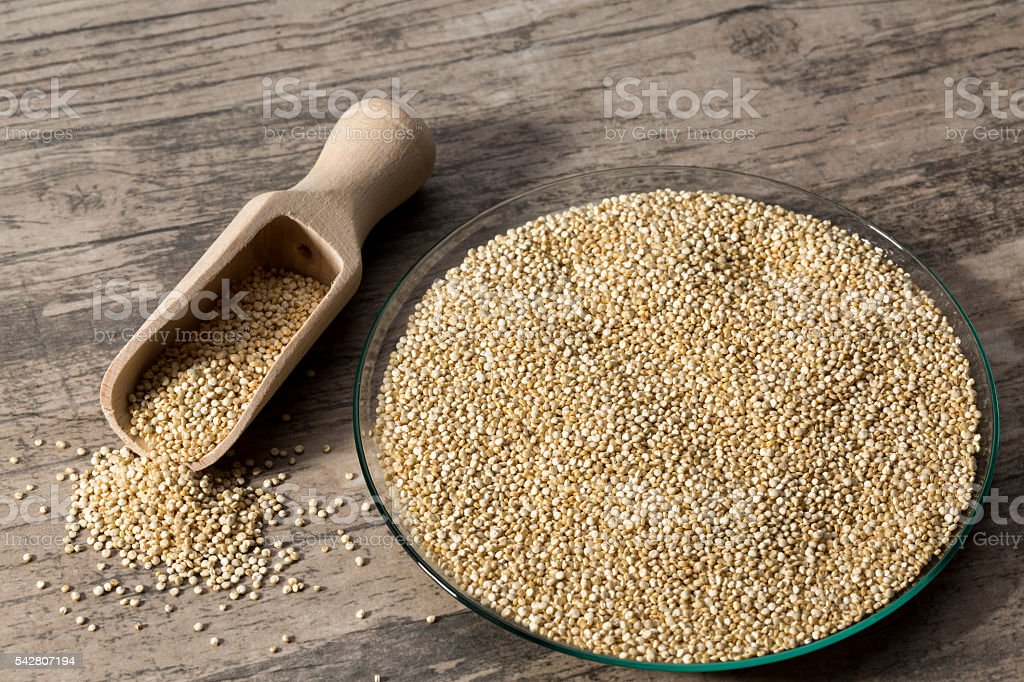 Quinoa in glass dish on wooden background with spice shovel. stock photo