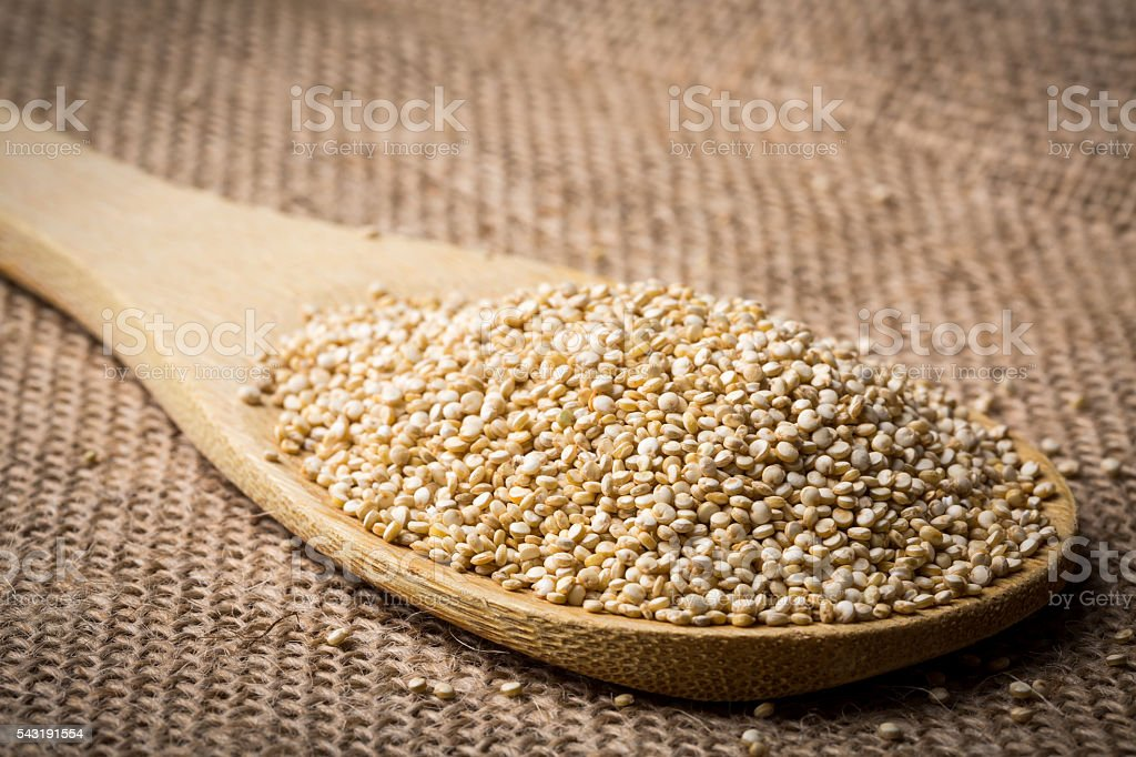Quinoa on wooden spoon and linen background. stock photo