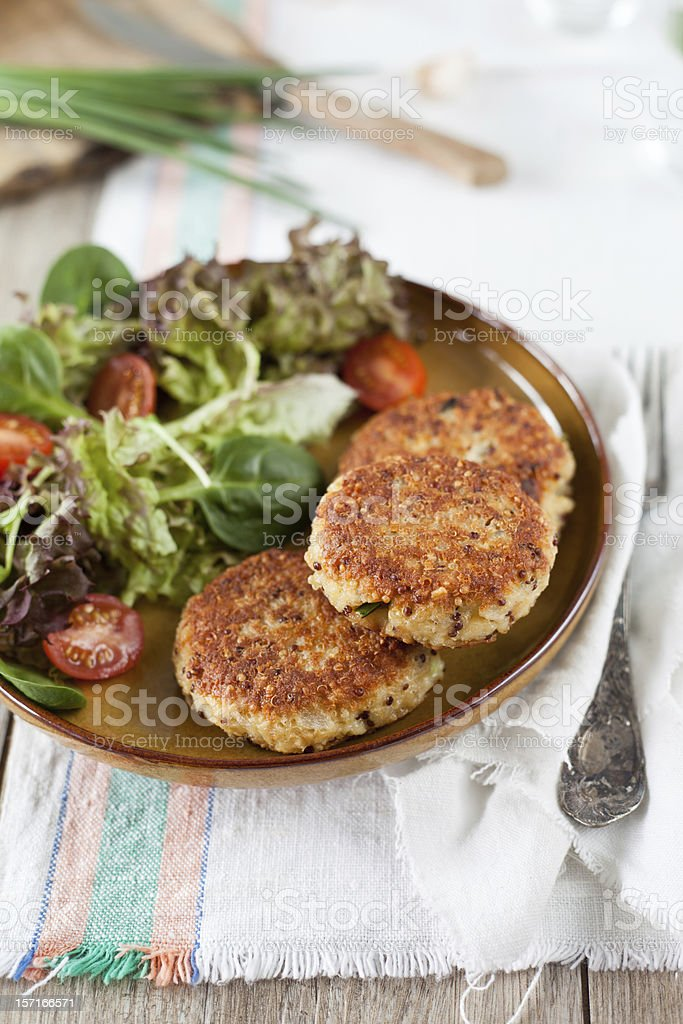 Quinoa patties on a brown plate with fresh salad stock photo