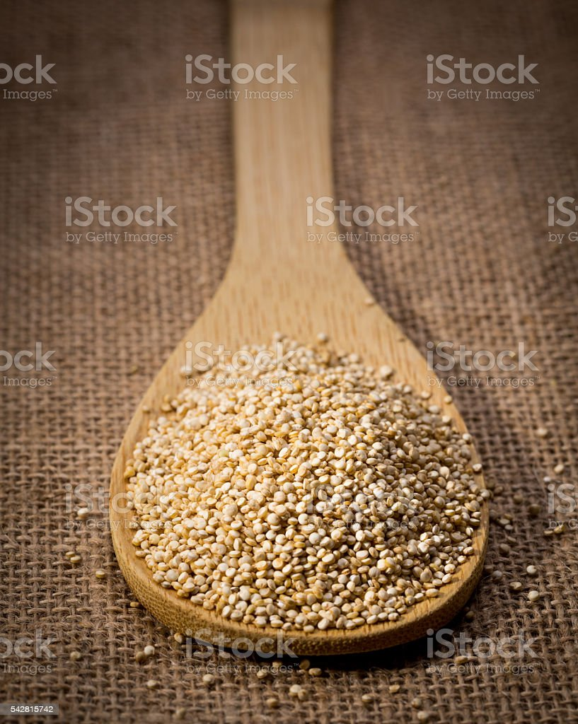 Quinoa seed on wooden spoon and linen background. stock photo