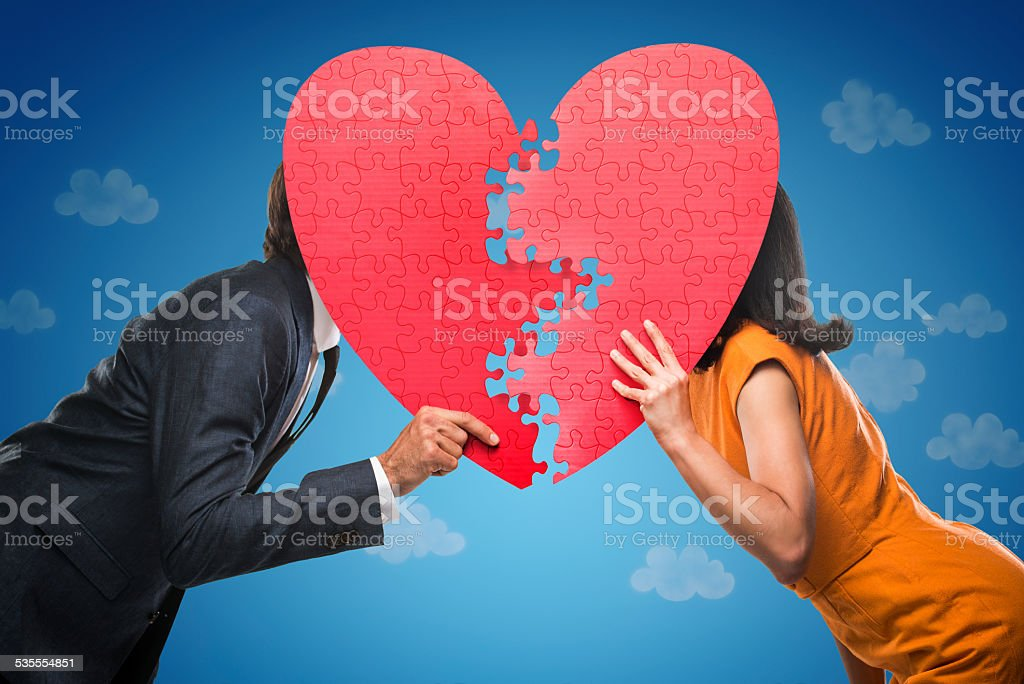 Quirky Couple Behind A Jigsaw Puzzle Heart stock photo