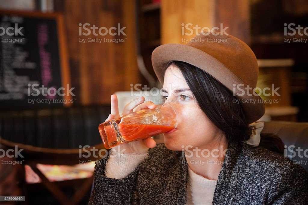 quirky girl with trilby hat enjoys tomato juice in cafe stock photo