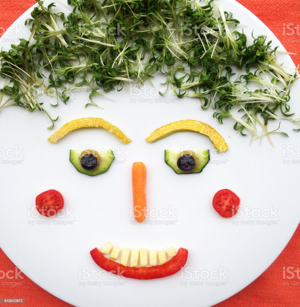 Quirky Moments:Funny food face made with vegetables and fruit and placed on a white plate stock photo