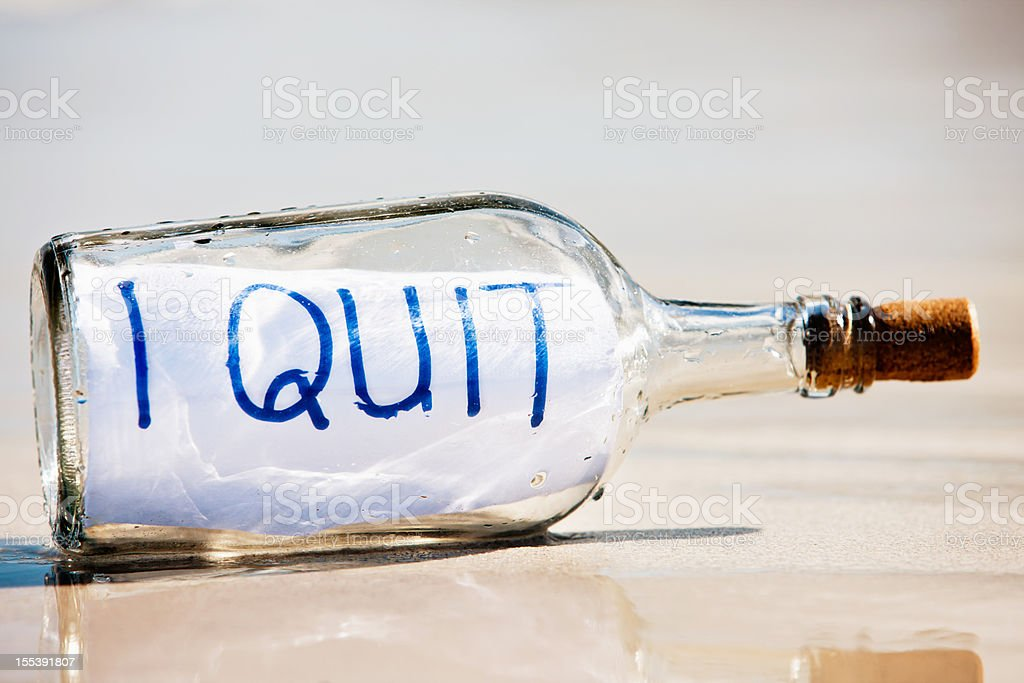 I Quit says close up message in bottle on beach royalty-free stock photo