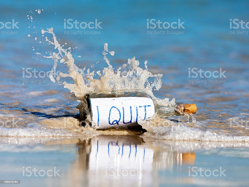 I quit, says message in bottle washed up on shore stock photo