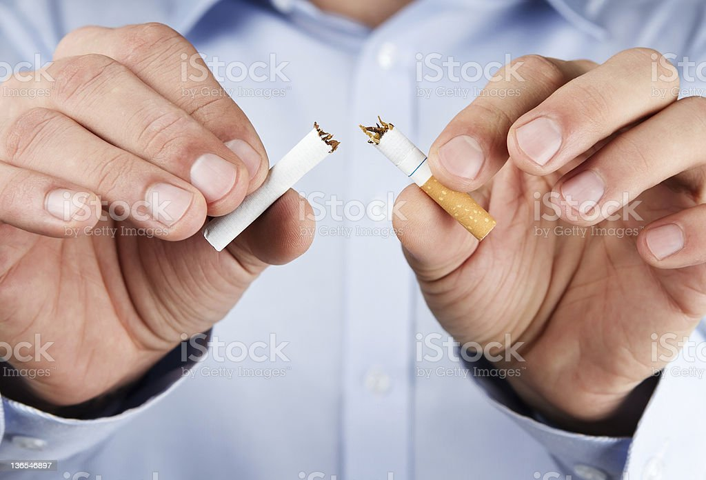 Quit smoking concept of man tearing cigarette in half stock photo