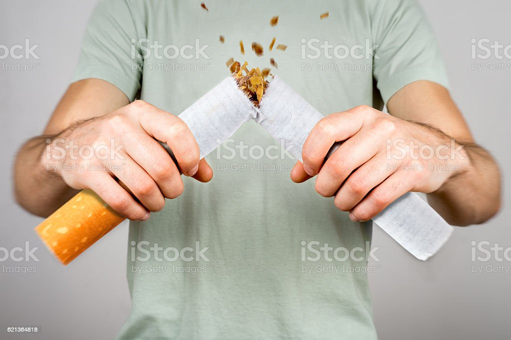 Quit smoking - male smoker breaking giant cigarette stock photo