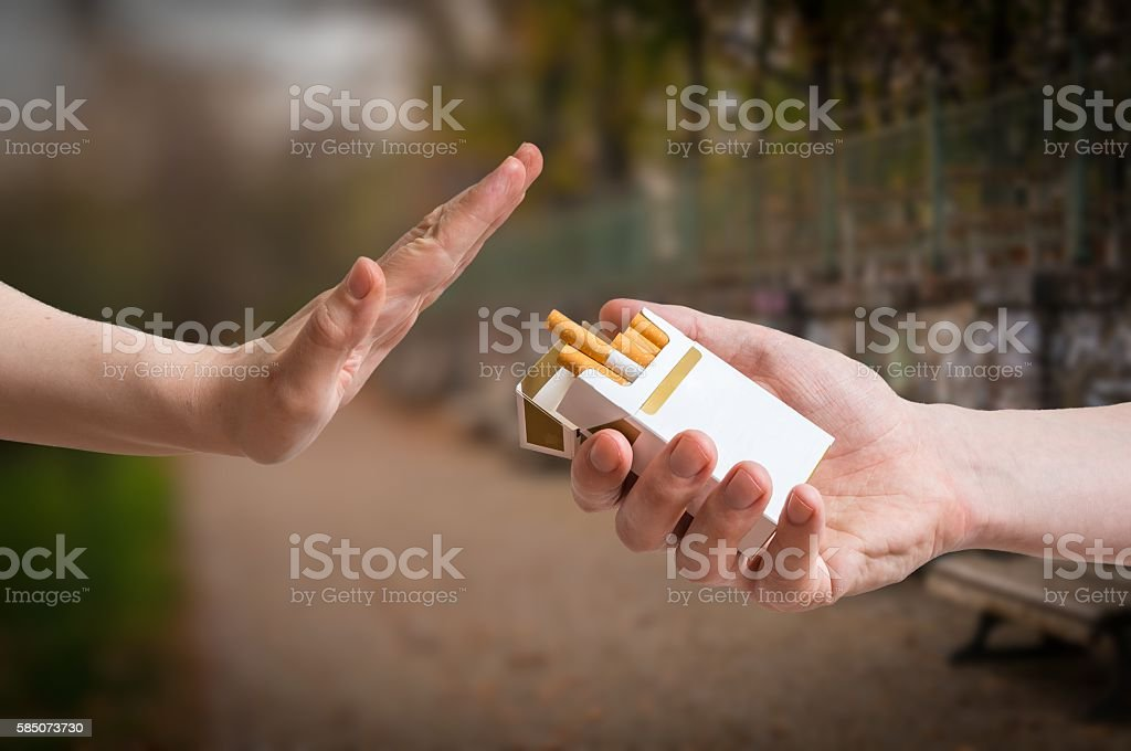 Quitting smoking concept. Hand is rejecting cigarette offer. stock photo