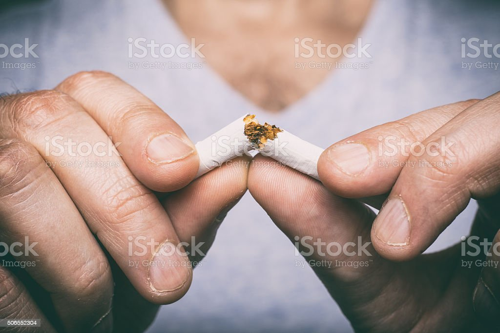 Quitting smoking - male hand crushing cigarette stock photo