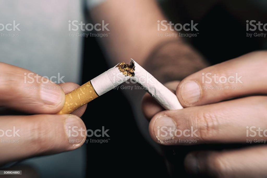 Quitting smoking - male hand crushing cigarette stock photo
