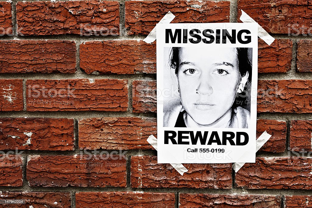 """""""Missing"""" poster of teenage girl taped to red brick wall stock photo"""