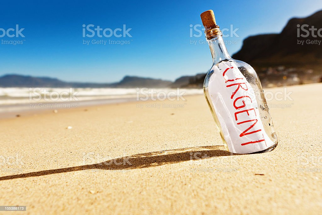 """Urgent"" says message in bottle on deserted beach! royalty-free stock photo"