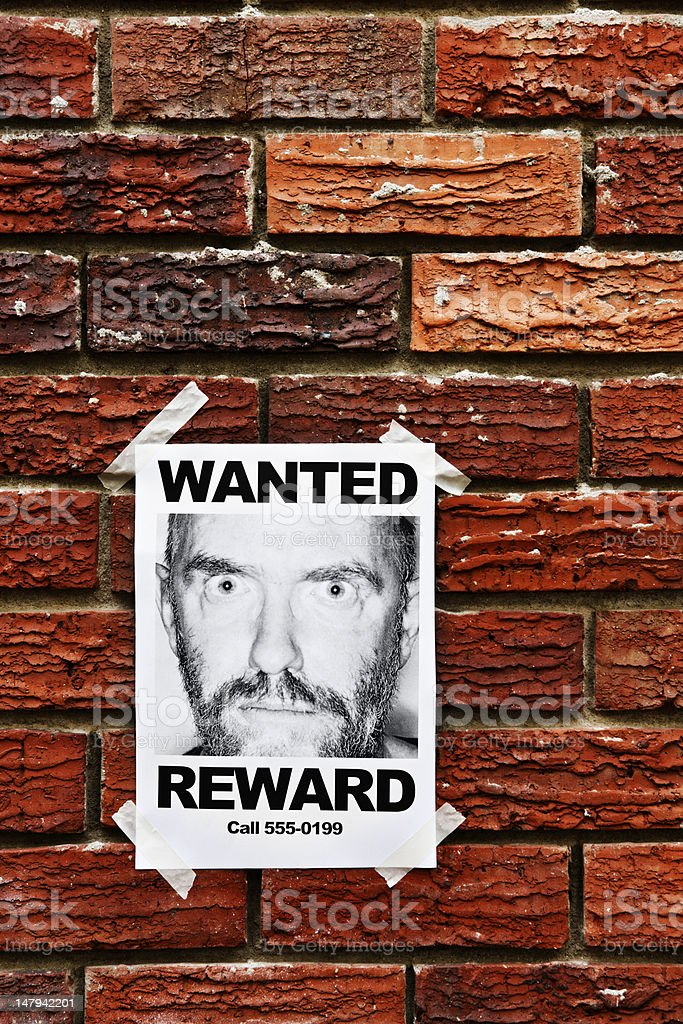 """""""Wanted"""" poster of wild-eyed man taped to brick wall royalty-free stock photo"""