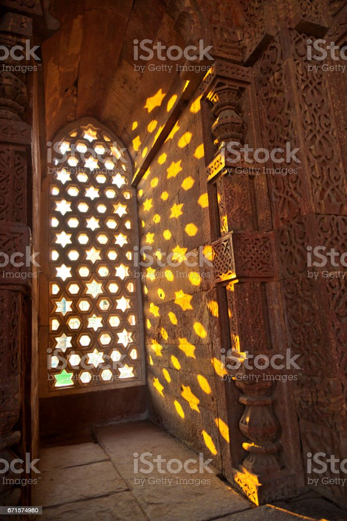 Qutb Minar, Delhi, carvings in the sandstone of a window gives a pattern of sky with stars stock photo