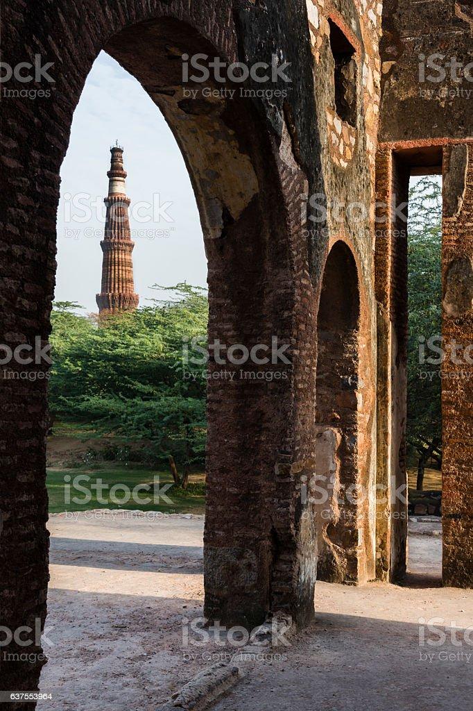 Qutub Minar as seen through ruins of mehrauli archaeological park. stock photo