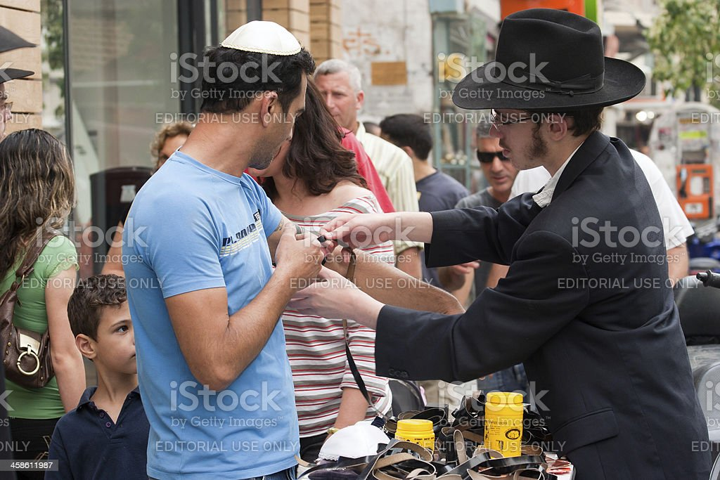 Rabbi Assists Man to Wrap Tefillin in Israel stock photo