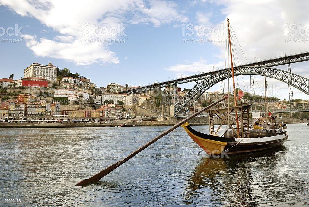 Rabelo boat on water near bridge and the city of Porto stock photo