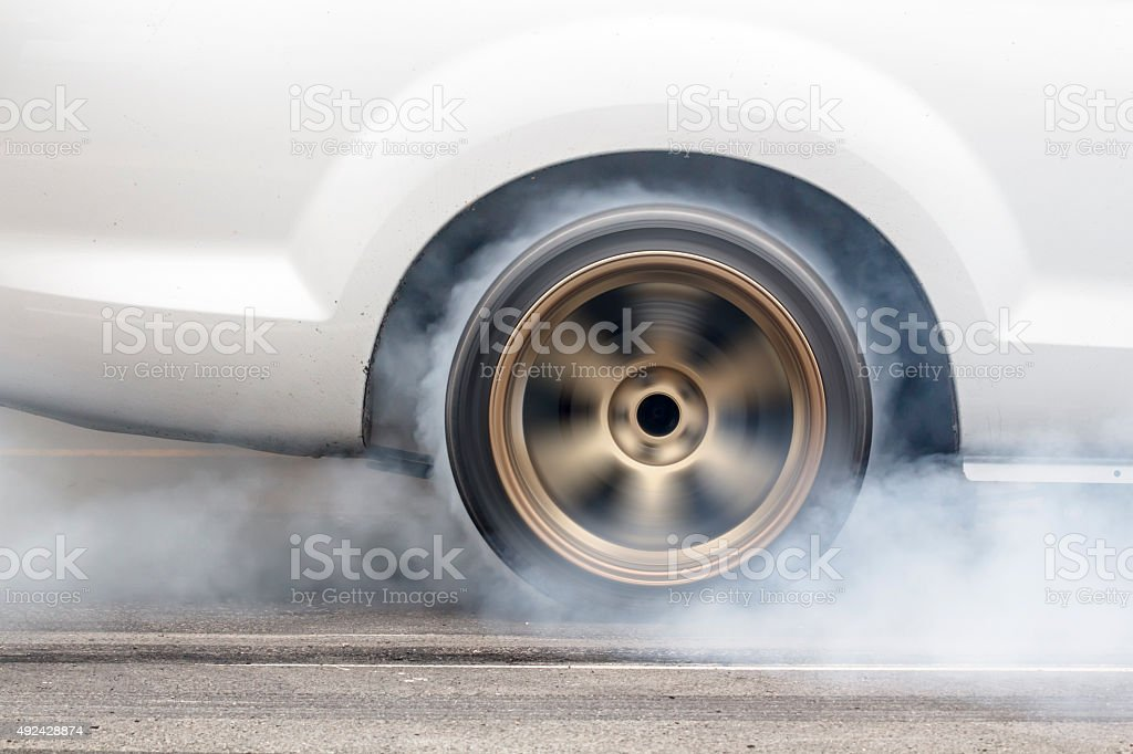 race car burns rubber off its tires stock photo