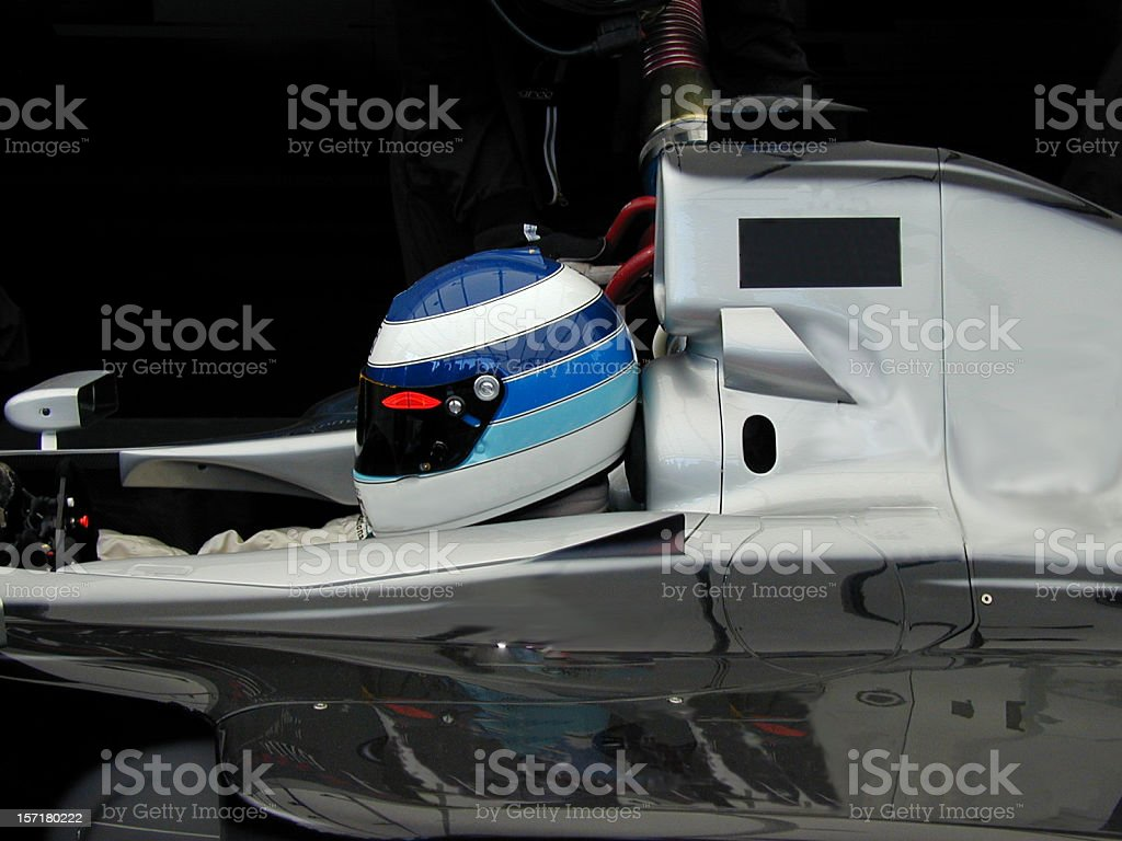 Race car driver wearing helmet and sitting in a car stock photo