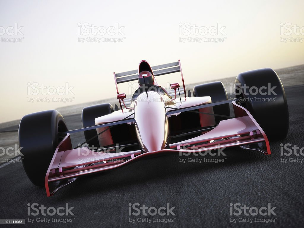 Race car racing on a track front view stock photo