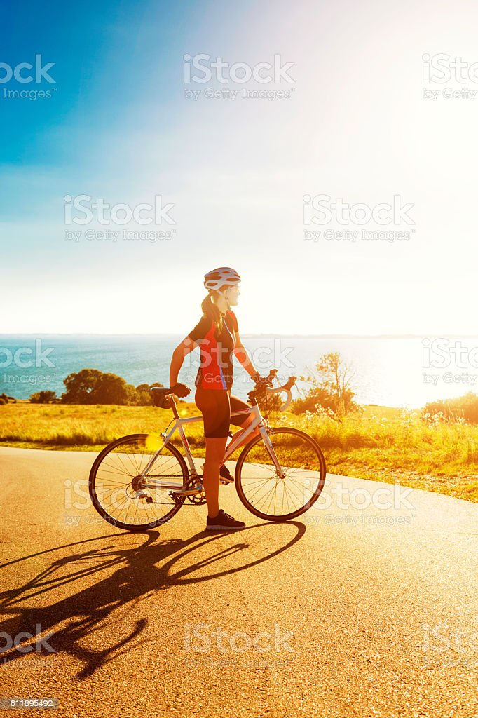 Race cyclist stands next to bike and looks at sunset stock photo