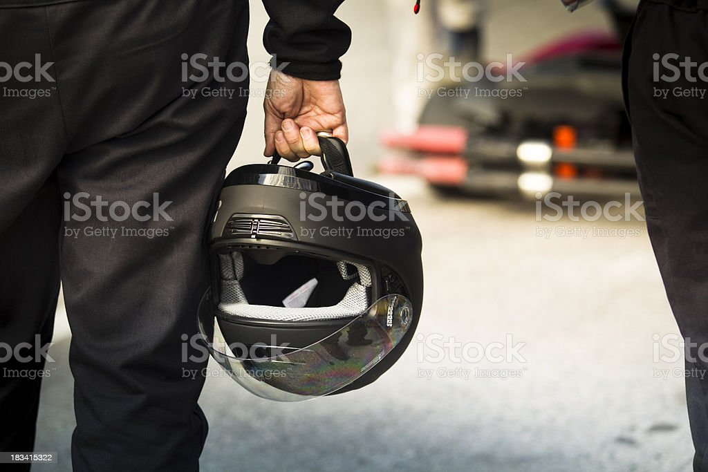 Race driver holds a helmet on the track stock photo