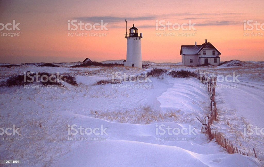 Race Point Lighthouse and House with Snowy Landscape at Sunset stock photo